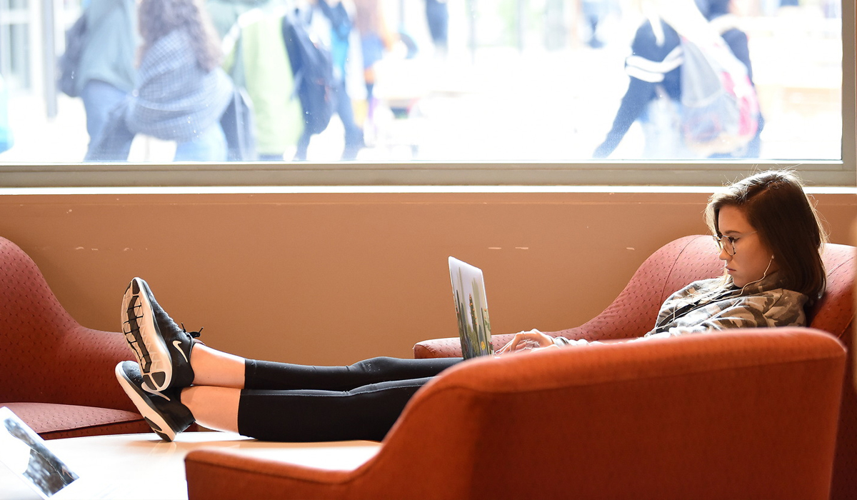 Female student studying and reading with legs up on sofa